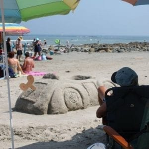 People On Wells Beach With Sand Sculpture